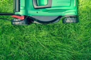 Lawn mower against long grass